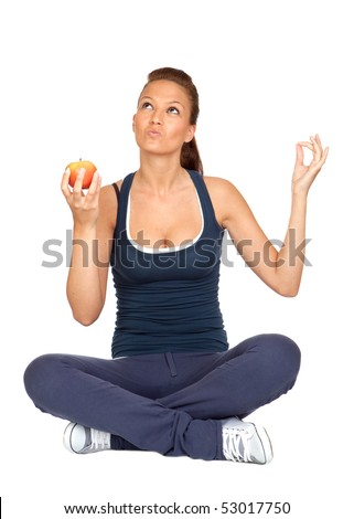 Gymnastics girl with an apple sitting with cross-legs on white background - stock photo
