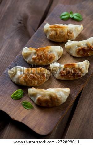 Gyoza dumplings on a rustic wooden cutting board, above view - stock photo