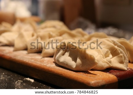 gyoza wrappers on flour chopping board