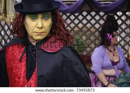 Gypsy carnival clown magician sad strange man and woman - stock photo