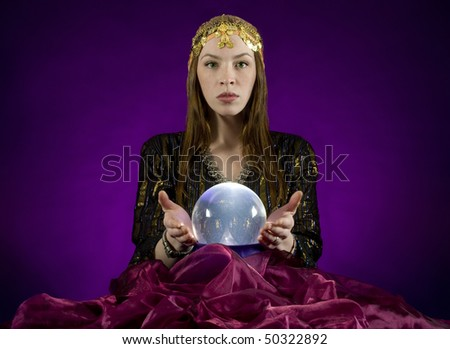 Gypsy fortune-teller,  gazes into crystalball. - stock photo