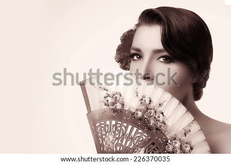 Gypsy girl. Beautiful Andalusian woman with carnation in hair and covering half face with a stylish fan. Spanish beauty. Fine Art portrait in sepia with copy space for text. - stock photo
