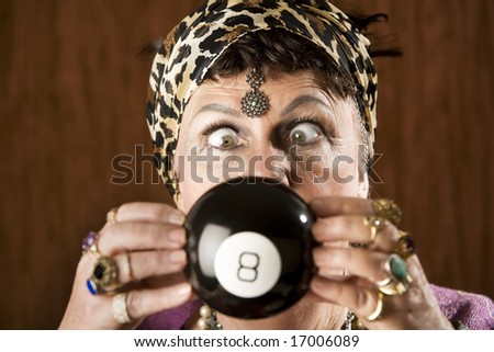 Gypsy looking at an eight ball to predict the future - stock photo