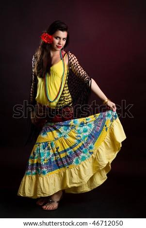 Gypsy woman dance in yellow dress on dark background - stock photo