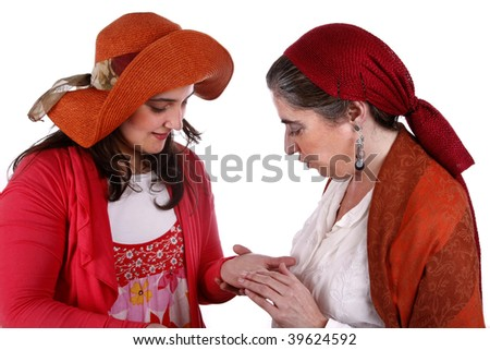 Gypsy woman reading the lines in a young woman's hand - stock photo