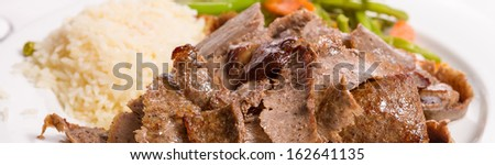 Gyro doner garnished with rice pilaf and vegetables - stock photo