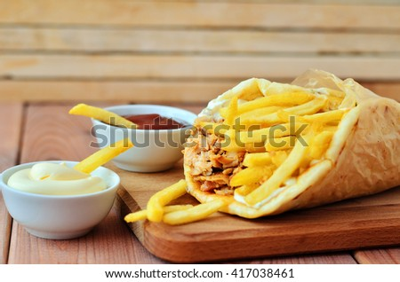 Gyro on a wooden table. Gyro, fries and two sauces on wooden background - stock photo