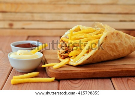 Gyro with chicken and french fries on a wooden board next to the ketchup and mayonnaise - stock photo
