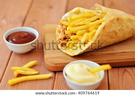 Gyro with fries and two sauces on wooden background - stock photo