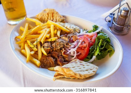 Gyros with chips on the plate - stock photo