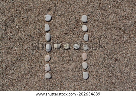 H letter made of stones on sand  - stock photo