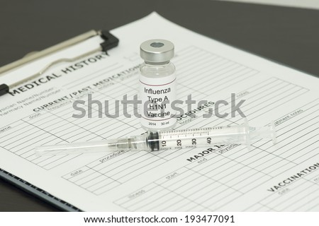 H1N1 pandemic influenza vaccine with syringe and patient chart.