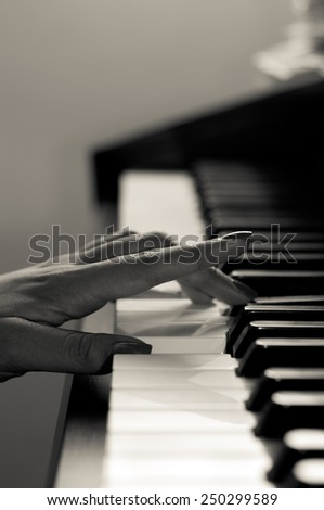 Ha black and white toned image of a female hand playing the piano - stock photo