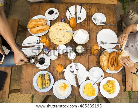 Ha Giang, Viet Nam - Apr 17, 2016: Young happy family having breakfast on wooden table in Hagiang, Vietnam.