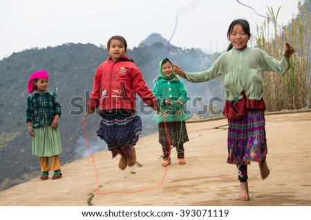 HA GIANG, VIET NAM, March 14, 2016 Hmong ethnic group of children, highland Ha Giang (name unknown), have fun jumping seconds, outdoor - stock photo