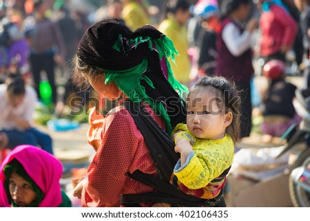 Ha Giang, Vietnam - Feb 14, 2016: Hmong little girl on her mother back in a local market in Dong Van district