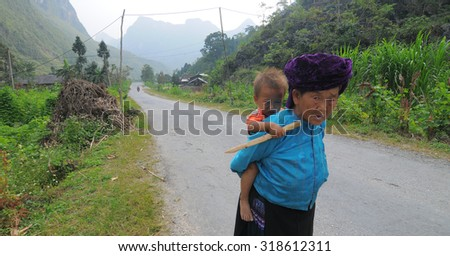 HA GIANG, VIETNAM - SEP 2, 2015. People walking on countryside road to coming home after finish work in Ha Giang, north of Viet Nam.