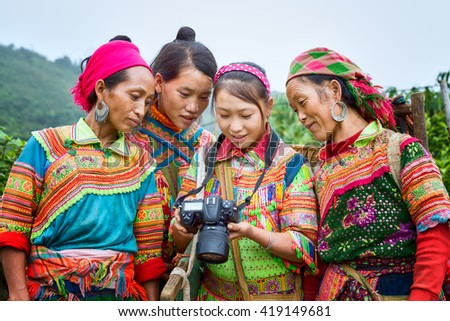 Ha Giang, Vietnam - September 23rd, 2015: Ethnic watching camera image with gentle smile, colorful clothing, they very happy to see their image after hours hard labor mountains in Ha Giang, Vietnam - stock photo