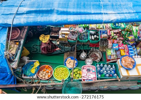 HA LONG BAY, VIETNAM - JANUARY 29, 2014: A Vietnamese woman selling goods from her boat at Ha Long Bay in January 2014. - stock photo