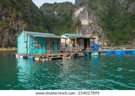 HA-LONG BAY, VIETNAM - JANUARY 28: Run down houses in a floating village on January 28, 2014 in Ha-long Bay, Vietnam. - stock photo