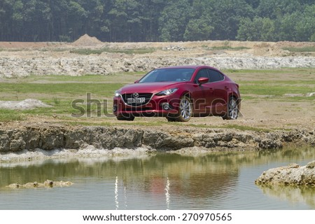 Ha Noi, Viet Nam - April 13, 2015: Mazda3 all new (2015) car running on the mud road in Vietnam - stock photo