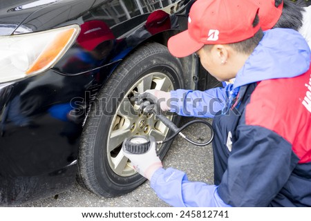 Ha Noi, Viet Nam - Dec 13, 2014: A Man checking tire pressure, car mechanic inflating tyre with alloy wheel in Vietnam - stock photo