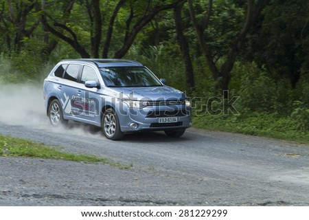 Ha Noi, Viet Nam - May 18, 2015: The Mitsubishi Outlander PHEV plug-in Hybrid CUV running on the bad road in Vietnam - stock photo