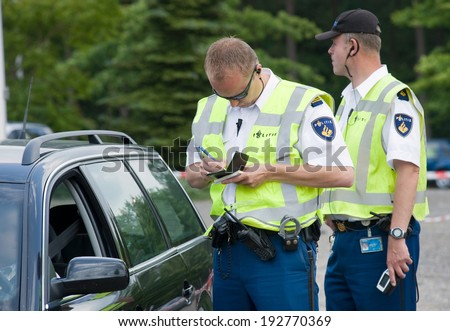 HAAKSBERGEN, NETHERLANDS - JUNE 09: A policeman is writing a ticket for a car driver who was speeding, june 09, 2011 in the Netherlands - stock photo