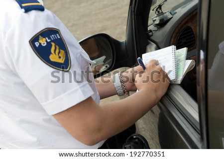HAAKSBERGEN, NETHERLANDS - JUNE 09: A policewoman is writing information from a car driver on a notebook to check, june 09, 2011 in the Netherlands - stock photo