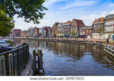 Haarlem, Netherlands, on July 10, 2014. Typical urban view. Old houses in the canal embankment are reflected in its water