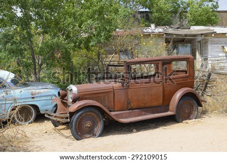 HACKBERRY, AZ - MAY 28: Two rusty old-timer cars at General Store at Hackberry, Route 66, on May 28, 2015, in Hackberry, AZ. The historic Route 66 is attracting visitors from all over the world. - stock photo