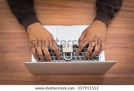 hacker and laptop on wooden background - stock photo