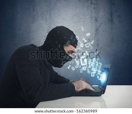 Hacker at work with a laptop and binary number