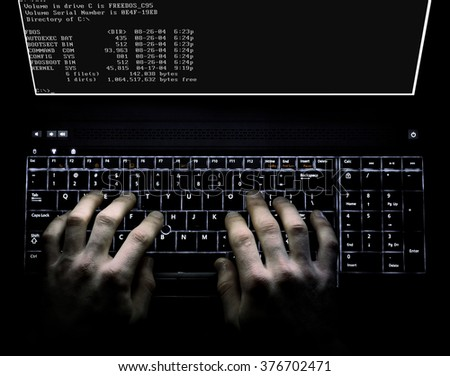 Hacker concept using a computer with stong lighting and dramatic impression - stock photo