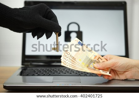 hacker gives key to victim to restore the personal data on laptop computer - stock photo
