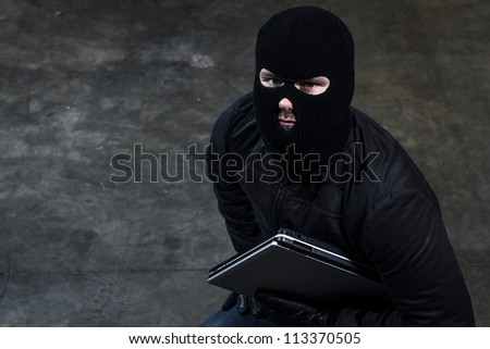hacker holding a computer - stock photo