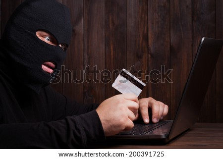 Hacker holding a credit card on wooden background - stock photo