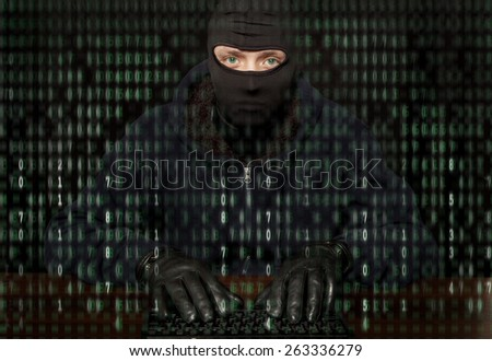 Hacker in a balaclava with laptop - stock photo