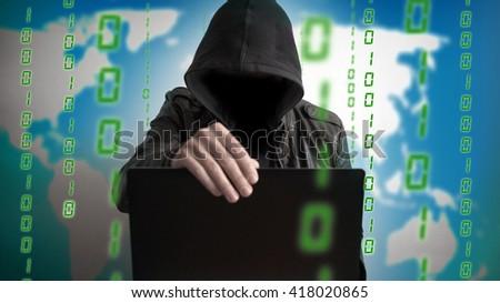 Hacker in a hood with laptop. Online network danger. - stock photo