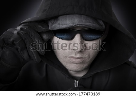 Hacker in a Sunglasses, Black Leather Gloves and Hood Face Closeup. Sunglasses Reflecting Computer Keyboard. Cyber Attack Theme. - stock photo