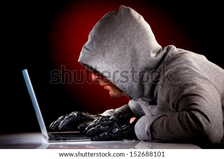 Hacker in a sunglasses with laptop. - stock photo