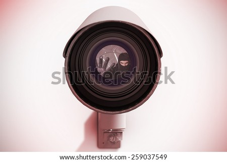 Hacker in balaclava gesturing and looking at camera against cctv camera - stock photo