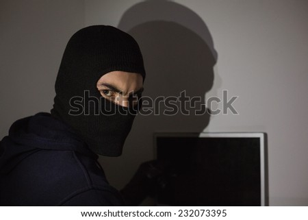 Hacker in balaclava hacking laptop while looking at camera in house - stock photo