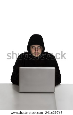 Hacker in black dress on a silver laptop computer isolated on white background - stock photo
