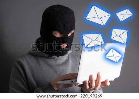 hacker in mask stealing data from laptop or sending spam messages - stock photo