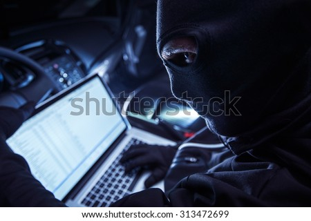 Hacker Inside the Car. Car Robber Hacking Vehicle From Inside Using His Laptop. Hacking On board Vehicle Computer. - stock photo