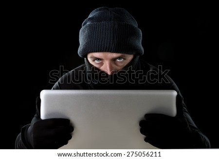 hacker man in black using computer laptop for criminal activity hacking password and private information cracking password too access bank account data in cyber crime concept