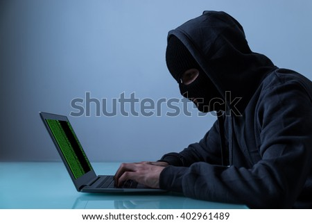 Hacker Stealing Information From Laptop In Office At Night