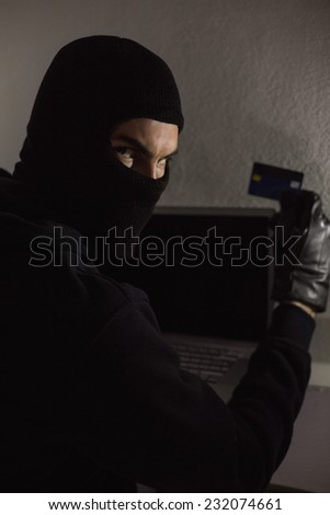 Hacker using debit card and laptop in house - stock photo