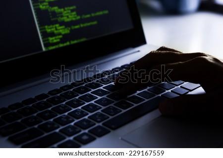 Hacker using laptop.  - stock photo